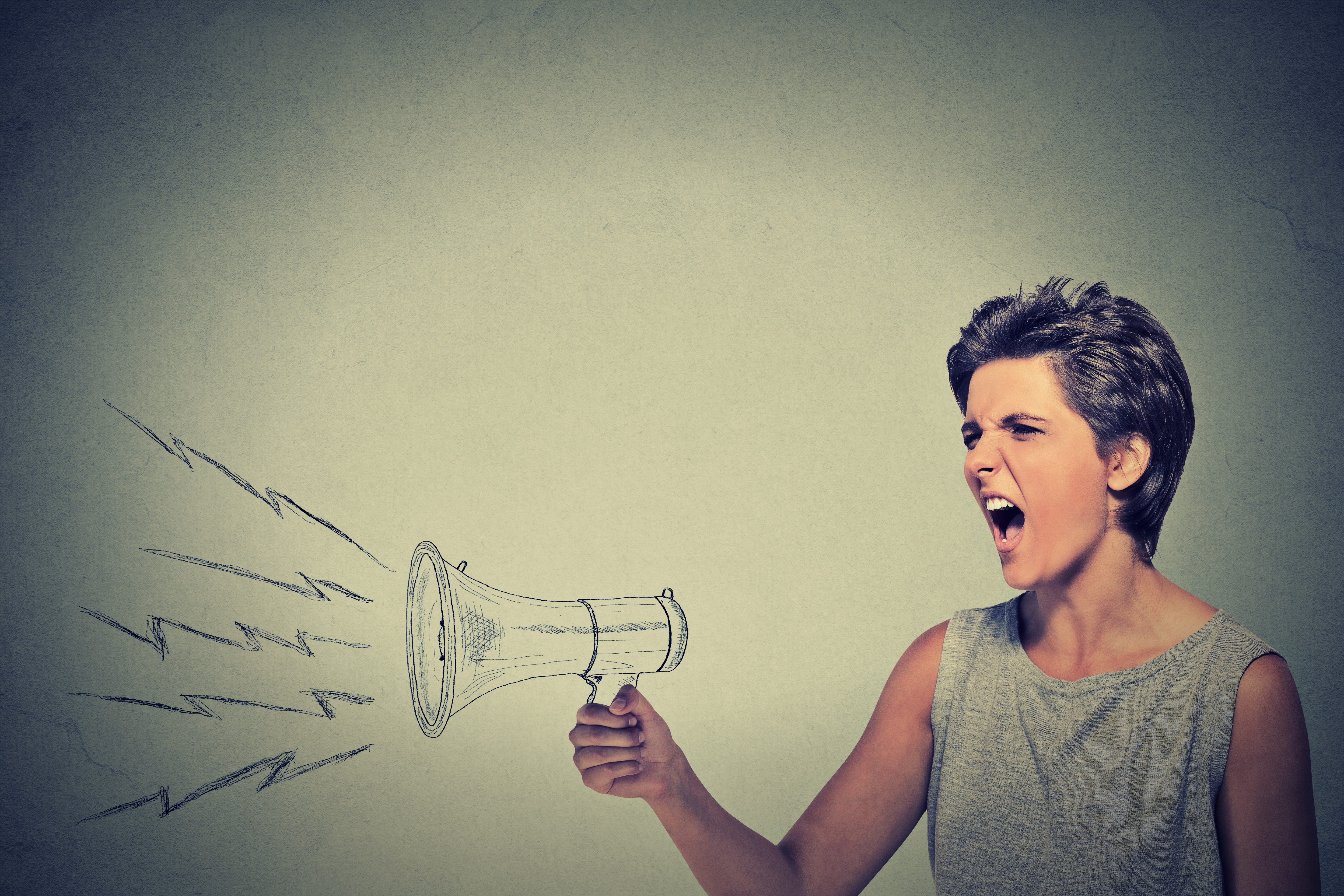 Portrait angry young woman holding screaming in megaphone isolated gre